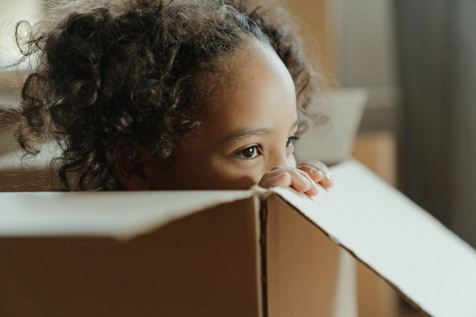 Young child looking over the edge of a cardboard box she is sitting in