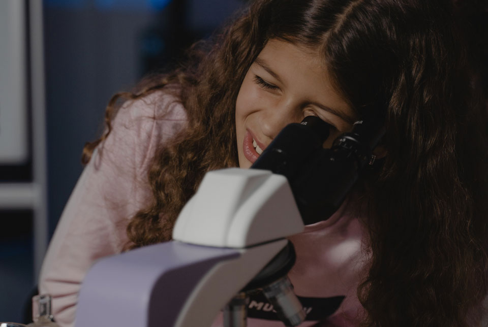 Teenager looking down a microscope
