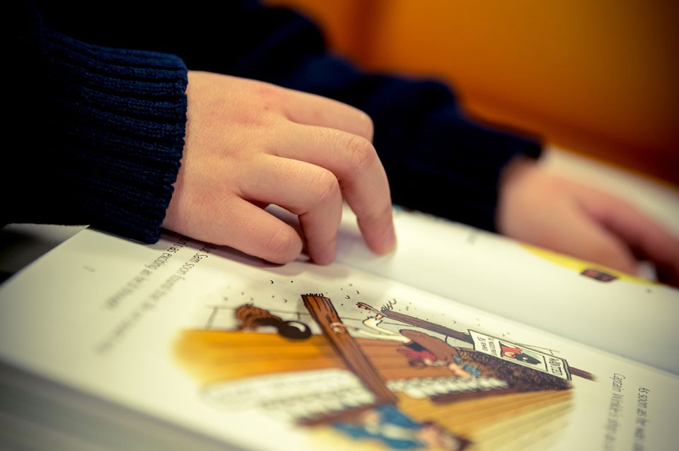 Child's hands resting on an illustrated book