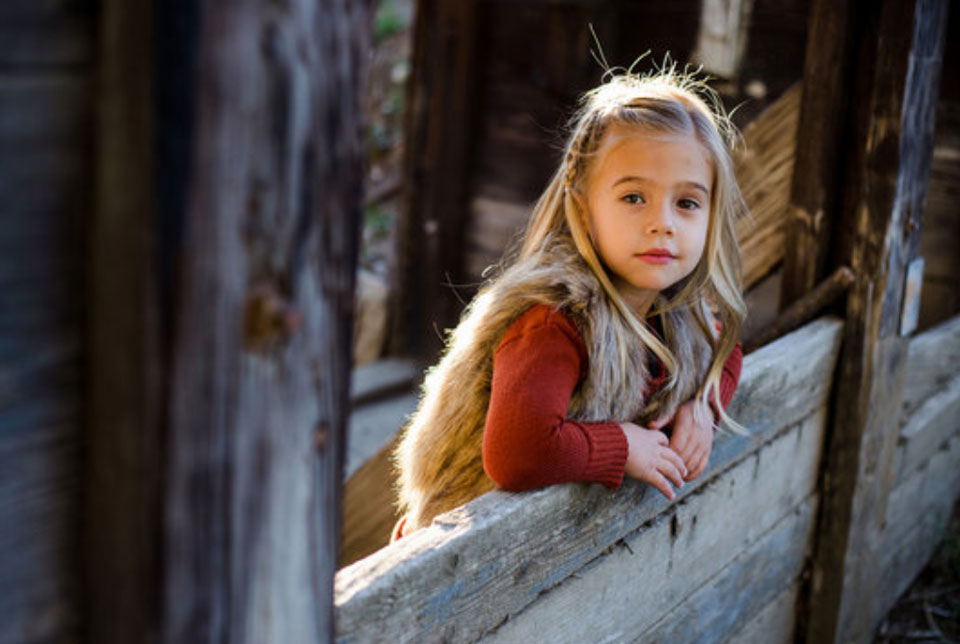 Young girl leaning against a wooden fence