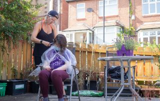 Hair cut in back garden, with one person wearing PPE mask