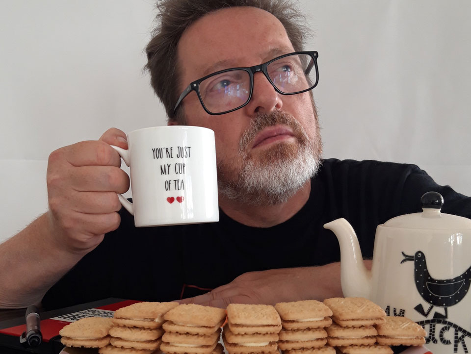 Poet Paul Cookson, raising a cup of tea, behind a wall of custard cream biscuits