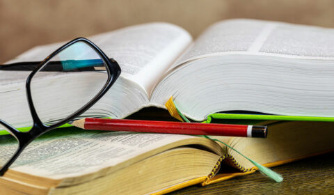 open books, lying overlapping with a pair of spectacles and a pencil