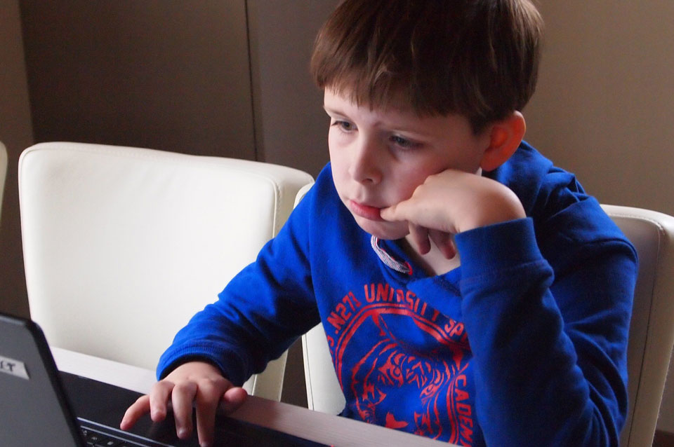 Boy sitting in front of a laptop looking sad