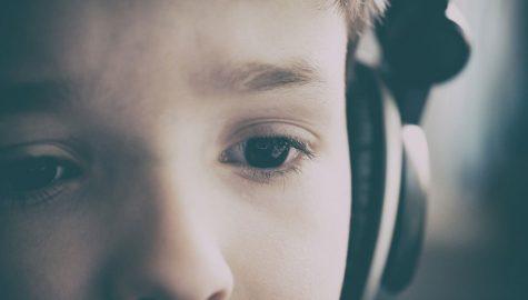 child in headphones looking slightly worried