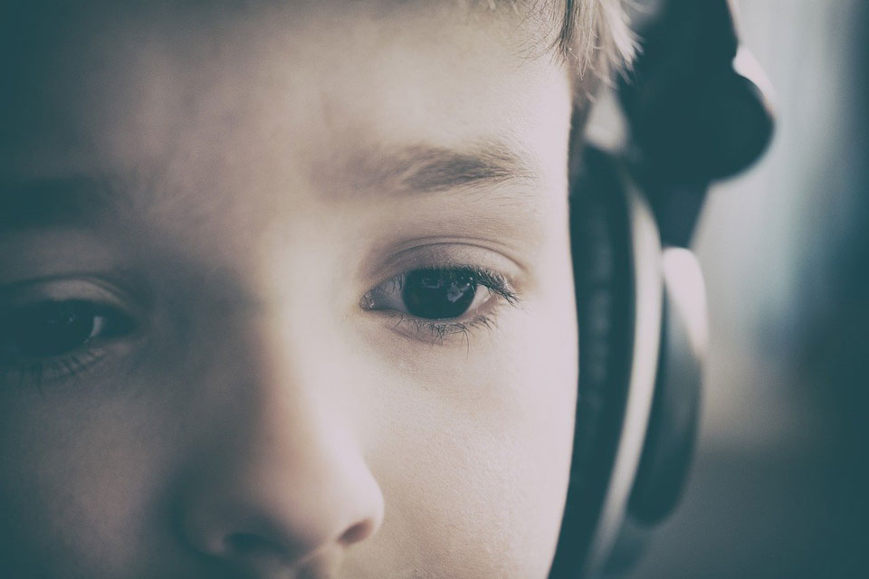 child in headphones looking slightly worried