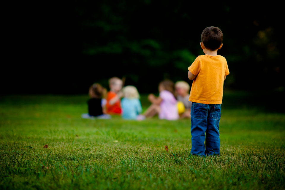 Young child standing isolated from a group playing on grass in front of him