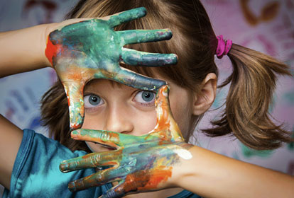 Child holding up painted hands used to frame face