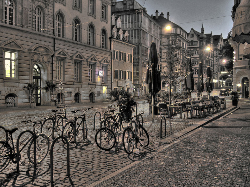 Bicycles in bike racks in the centre of Freiburg with traditional architecture behind them