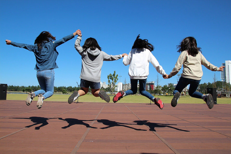 kids jumping high holding hands