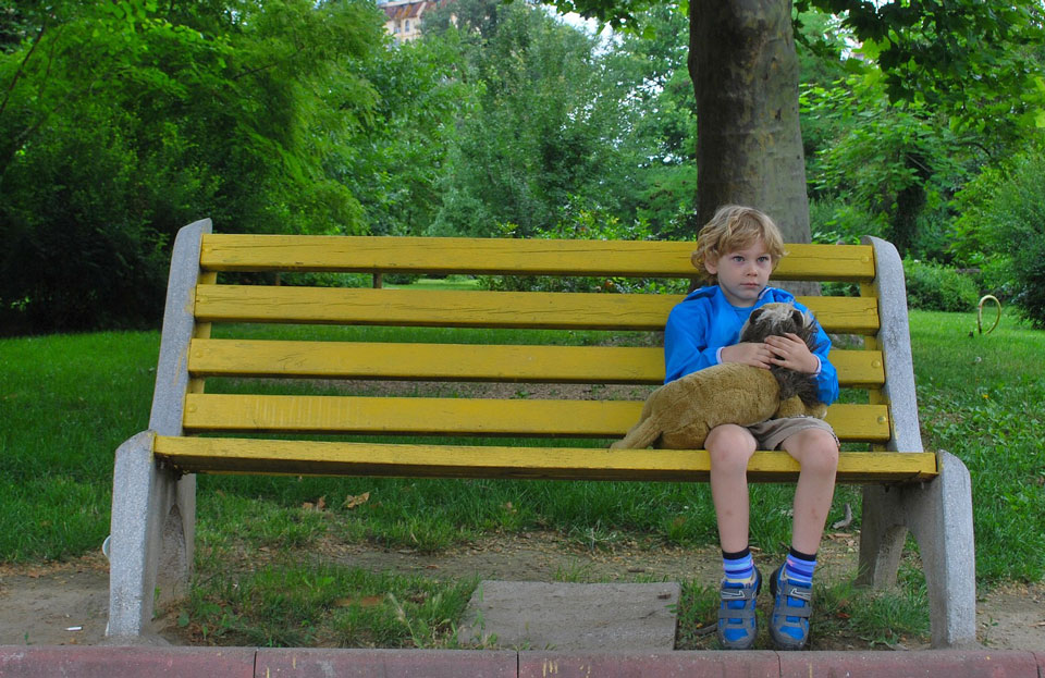 lonely child sitting on a park bench