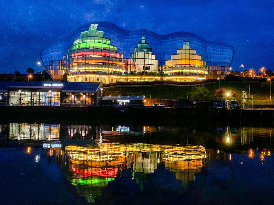 Nighttime shot. Lights of buildings, reflected on the Sage Building, Gateshead and the river Tyne below