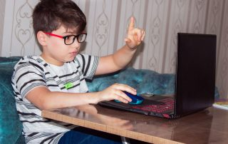 boy sitting in front of a laptop with hand raised