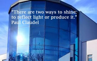 Sun reflected in glass building on MK campus of Open University. Words say There are two ways to shine, to reflect light or produce it