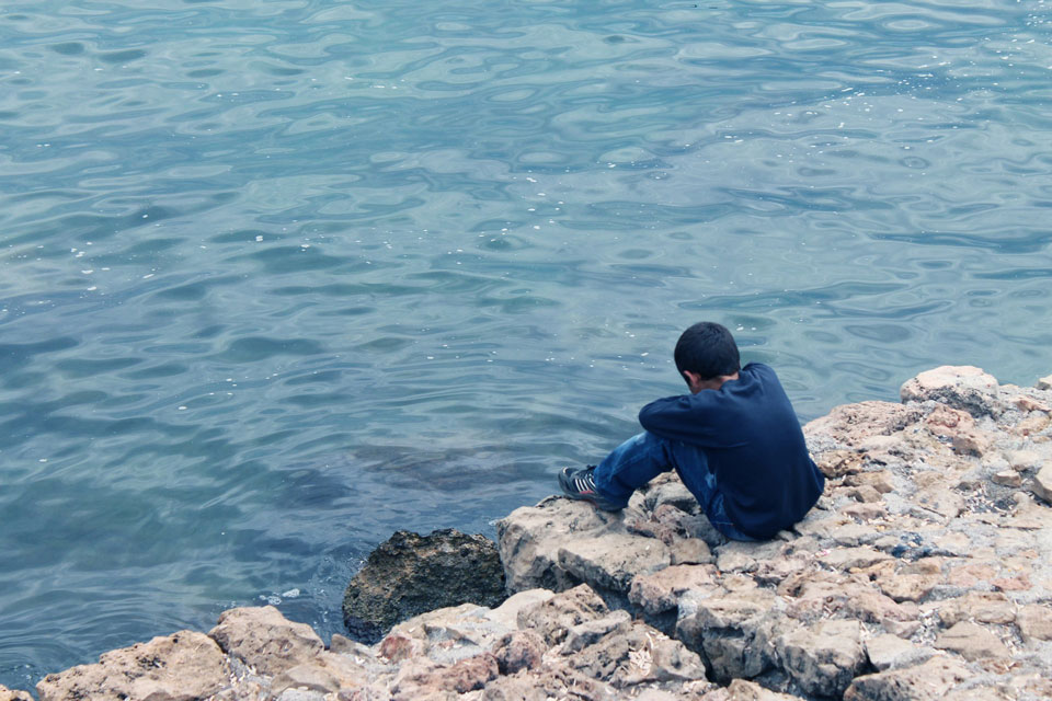 Child sitting on the edge of a stone jetty alone