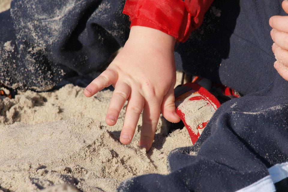 child tentatively touching sand