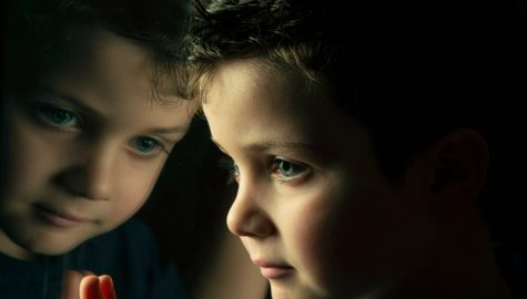 Child looking out of the window, with face reflected in the window