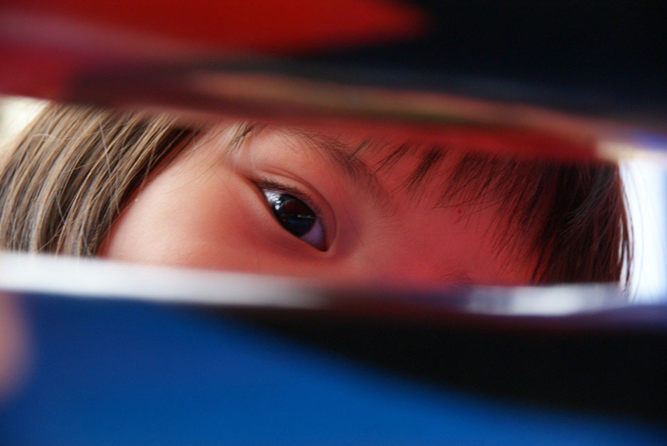 Part of a child's face as they look through a letterbox