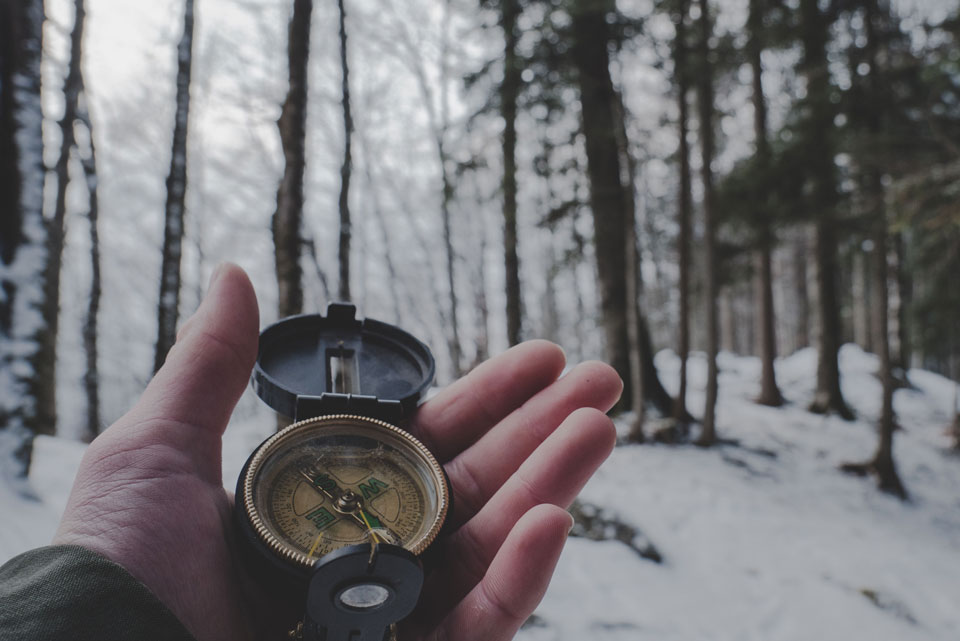 Hand holding a compass in a snowy woodland scene