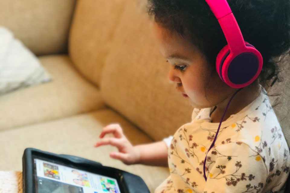 Young girl on sofa looking at a tablet, wearing headphones