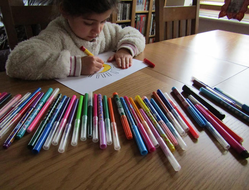 Child colouring in with felt pens in front of her like a rainbow