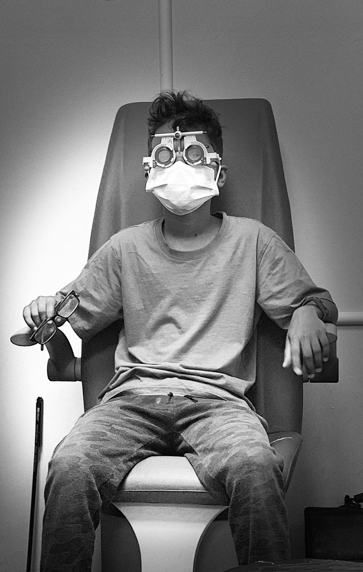 black and white photograph of man in opticians chair with mask on