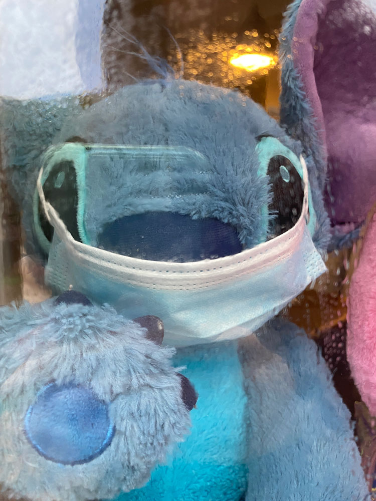 Stitch soft toy wearing a mask behind a glass window