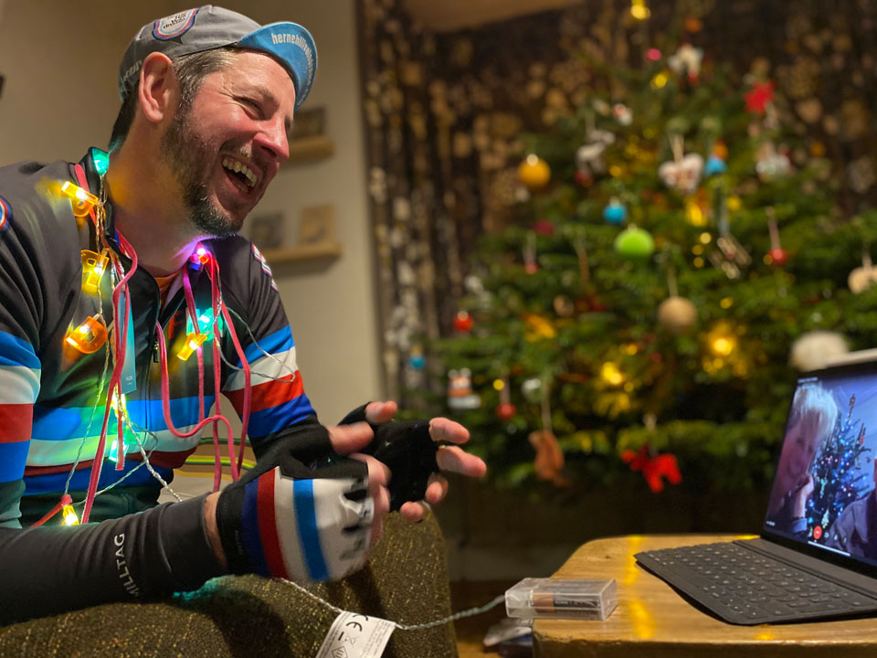 Man covered in lit fairy lights laughing at a laptop