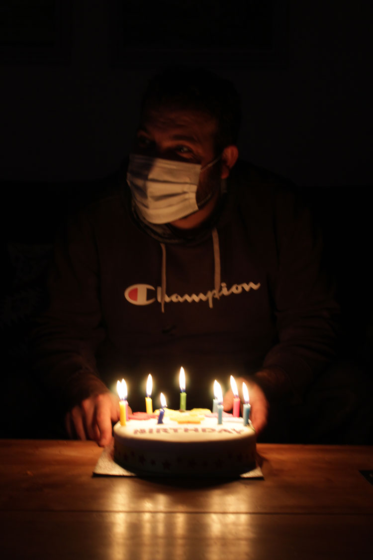 A birthday cake with candles in front of someone wearing a mask