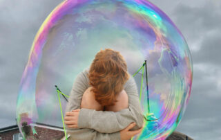 Child jumping crounched inside an irridescent soap bubble
