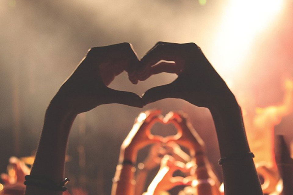 hands held high at a festival doing the mobot heart shape