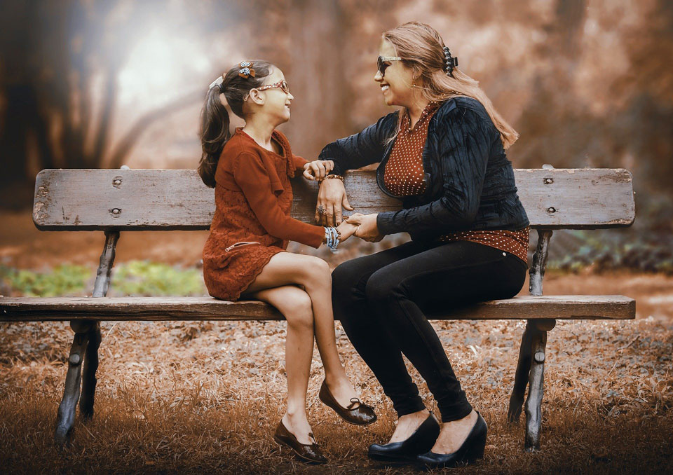 Parent and child sitting opposite each other on a bench talking