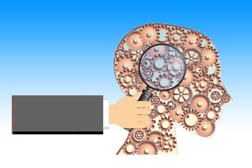 Hand holding a magnifying glass towards a stylistic cog representation of the brain and head
