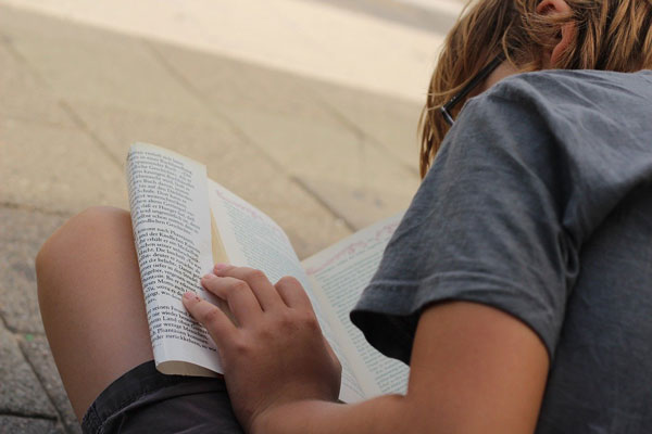 boy sitting on the ground reading a book