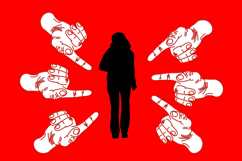 Silhouette of a woman standing alone with fingers pointing threateningly at her