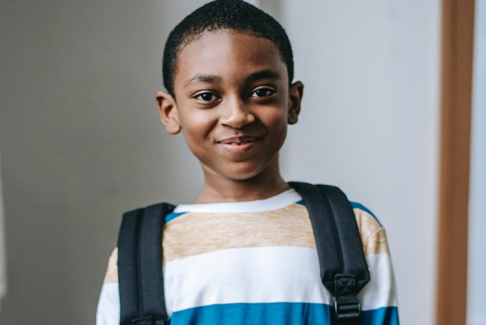 Smiling young lad wearing a rucksack