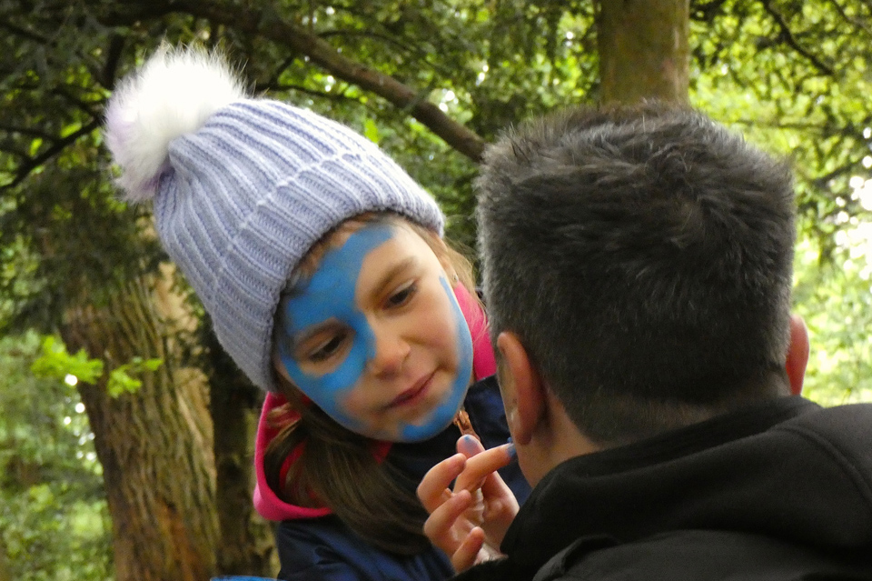 Child placing wode on her father's face