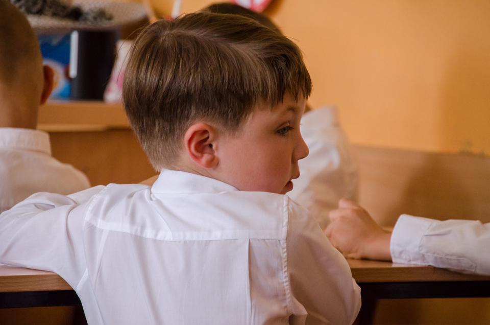 Boy sitting at a desk looking behind him