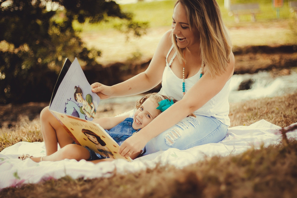 mother and daughter reading on the grass
