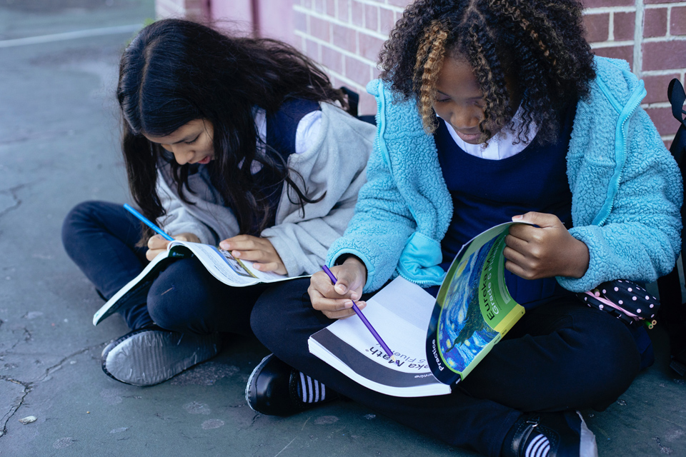 two teenager sitting on the ground going through workbooks