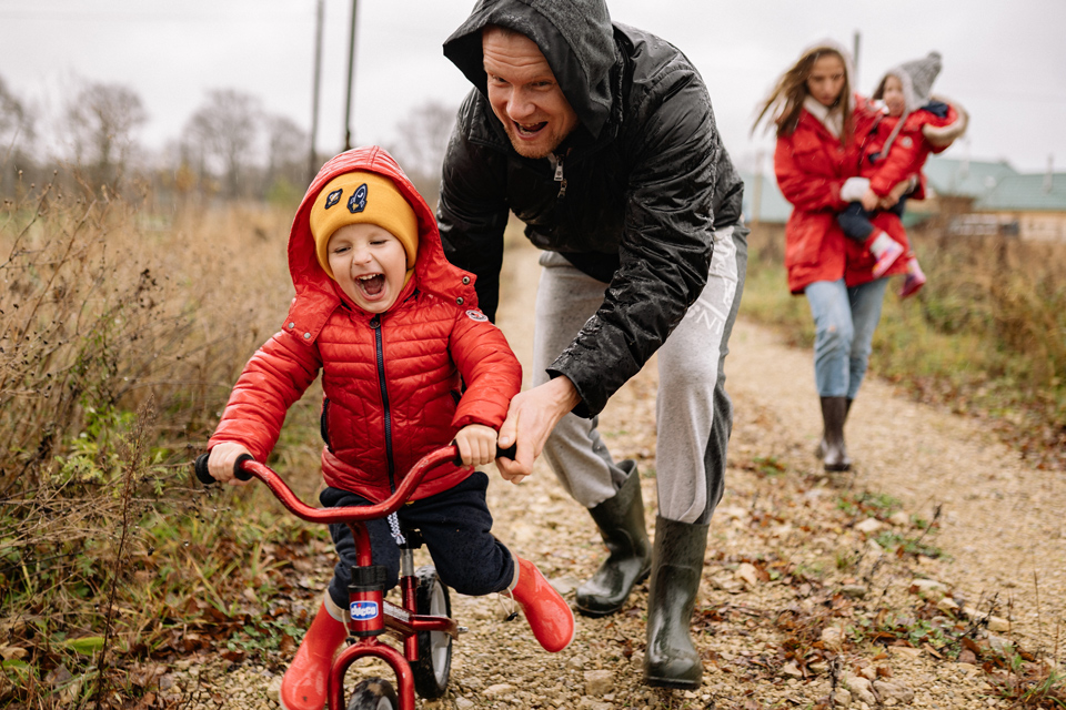 Family out in the winter fields, father pushing happy child on bike, mother walking behind carrying another child