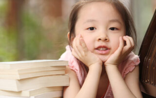 Young child leaning on her hands with a pile of books beside her