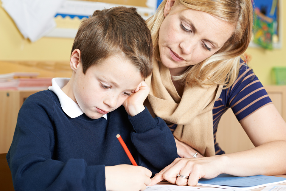 female teacher helping male primary school child with handwriting problem