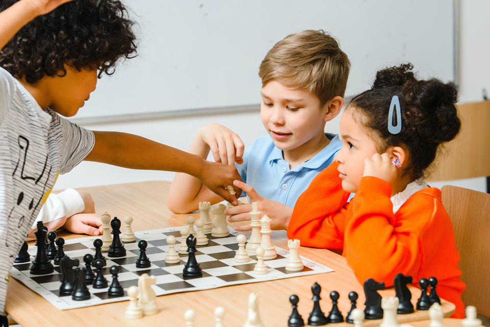 three children getting excited playing chess