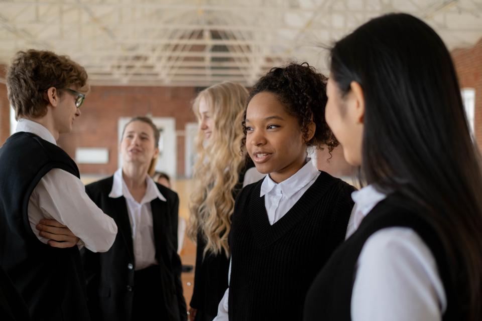 Secondary school children in uniform standing talking