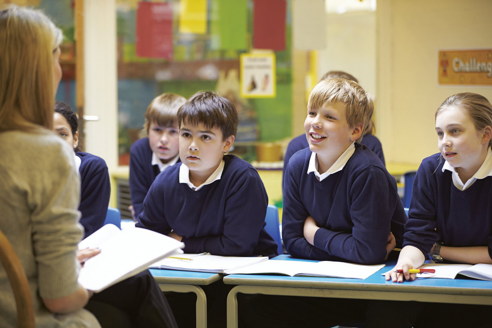 teacher sitting in front of pupils in uniform