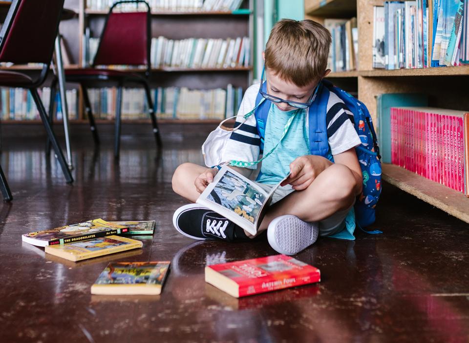 Boy sitting cross legged on floor of library