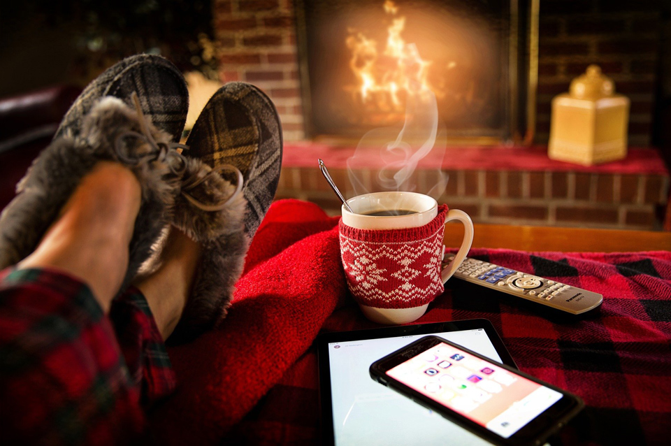 legs of person wearing slippers relaxing in front of fire with steaming drink on table