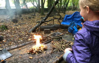 Girl looking at a fire just been started by her at Lea Green Centre, Let's Explore Day, October 2021